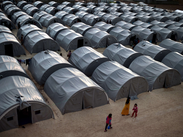 TOPSHOTS Syrian Kurdish refugees that fled the Syrian town of Kobane, also known as Ain al-Arab, walk past tents in a refugee camp in the southeastern town of Suruc, in the Turkish Sanliurfa province, on October 16, 2014. Kurdish fighters backed by a flurry of US-led air strikes were holding out on October 16 against jihadists in Kobane, as an Islamic State (IS) offensive on the Syrian border town entered its second month. AFP PHOTO / ARIS MESSINISARIS MESSINIS/AFP/Getty Images